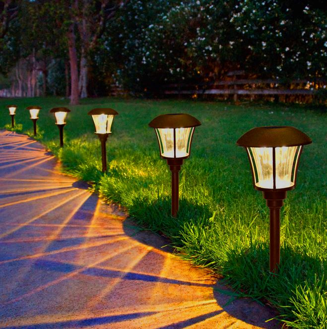 Solar powered outdoor path lights on edge of grass lawn